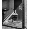 Untitled (Leaning Chair) (black and white photograph)