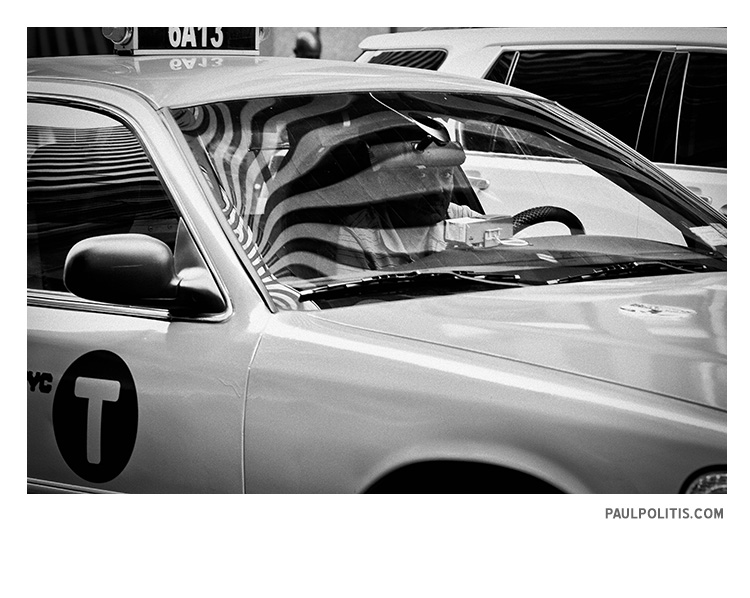 Cabbie and Flag Reflection (black and white photograph)
